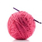 a ball of pink yarn with a crochet needle for a girls night in crochet party